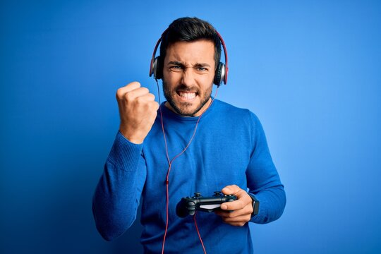 Young handsome gamer man with beard playing video game using joystick and headphones annoyed and frustrated shouting with anger, crazy and yelling with raised hand, anger concept