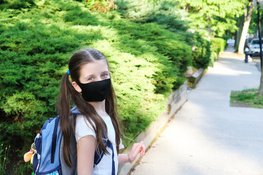 Elementary school student in a cloth dust mask with backpack in the street. Preteen girl is going to school in new normal. Education, coronavirus, back to school, hybrid model concept