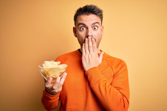 Young handsome man holding bowl with potatoes chips over isolated yellow background cover mouth with hand shocked with shame for mistake, expression of fear, scared in silence, secret concept