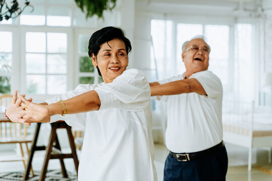 Positive elderly Asian man and woman stretching arms and smiling while dancing together in cozy room on weekend day at home