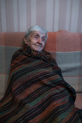An old woman is sitting on the sofa wrapped in a blanket.