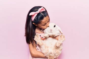Adorable hispanic kid girl wearing diadem smiling happy. Holding and kissing cute rabbit standing over isolated pink background