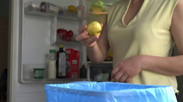 Throwing food waste in the trash. Household food loss. Food spoilage at home occurs due to improper storage. A woman throws uneaten expired fruits out of the refrigerator.