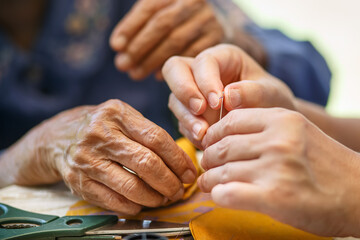Caregiver holding thread the needle for elderly woman in the cloth crafts occupational therapy for Alzheimers or dementia