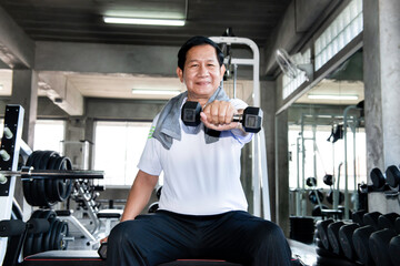 Asian senior male with dumbells in the gym. Mature male training with dumbbells in wellness club in fitness gym. Sport healthy lifestyle