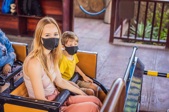 Mom and son on a roller coaster in medical masks after the coronovirus epidemic COVID 19