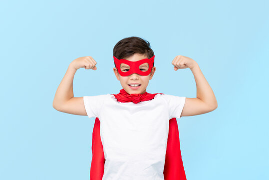 Cute superhero boy in red mask and cape flexing arm muscles isolated light blue background