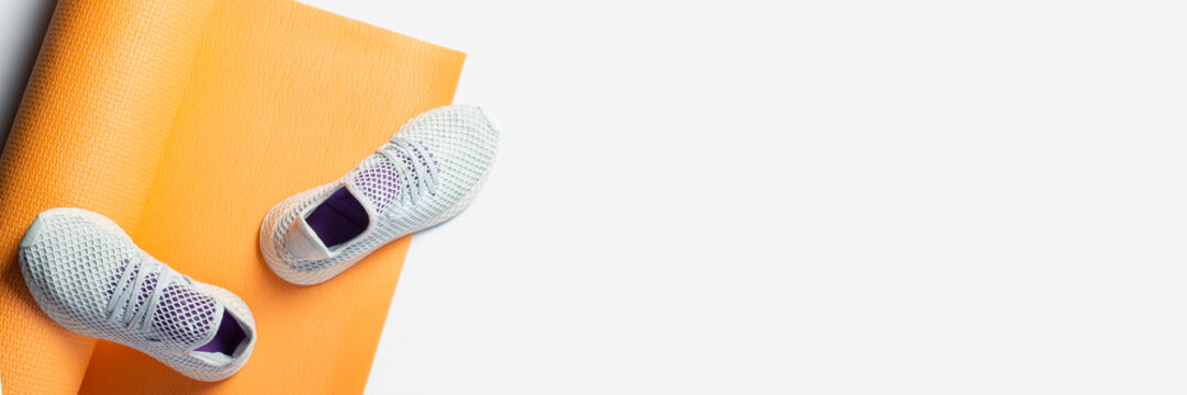 Yoga mat and sneakers on a white background. Sport and diet. Top view, flat lay. Banner