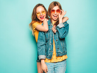 Two young beautiful smiling hipster girls in trendy summer yellow T-shirts and jeans jacket. Sexy...