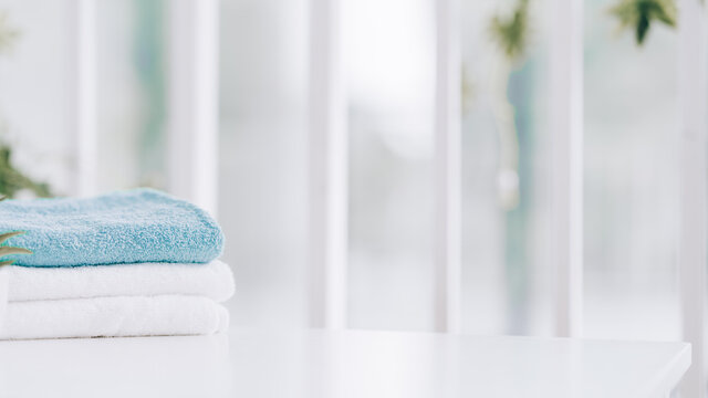 Stack of clean soft towels on blurred background