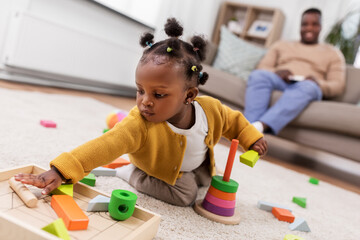 childhood and people concept - little african american baby girl playing with toy blocks at home