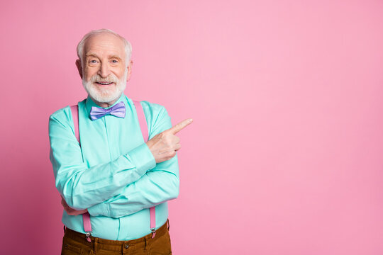 Photo of cool stylish look grandpa indicating finger empty space offer black friday low prices wear mint shirt suspenders violet bow tie isolated pastel pink color background