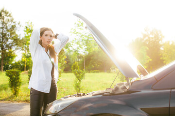 Frustrated young woman looking at broken down car engine on street