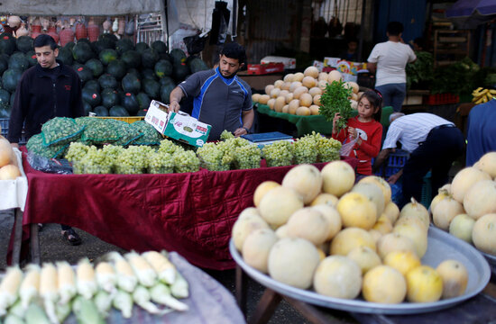 People shop as a vendor sells fruits and vegetables in a market as Palestinians ease COVID-19 restrictions, at the Beach refugee camp in Gaza City