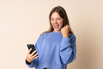 Young Lithuanian woman using mobile phone isolated on beige background celebrating a victory
