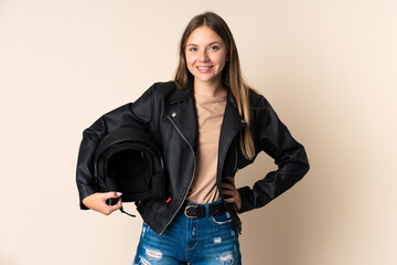 Young Lithuanian woman holding a motorcycle helmet isolated on beige background posing with arms at hip and smiling
