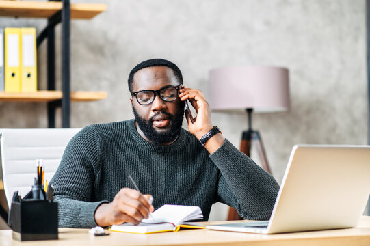 Young black man is solving business tasks on the phone, concentrated guy sits at the desk with laptop in contemporary office, talking on the phone and taking some notes