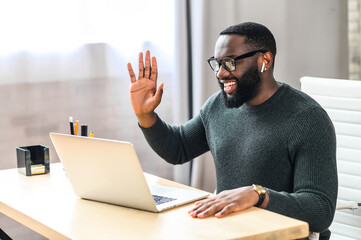 Video call. Cheerful attractive African-American guy is using laptop for video communication, a guy in glasses sits at the table in modern office, waving into webcam and talking online