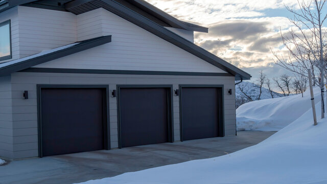Panorama Home exetrior with paved driveway leading to the three door garage entrance