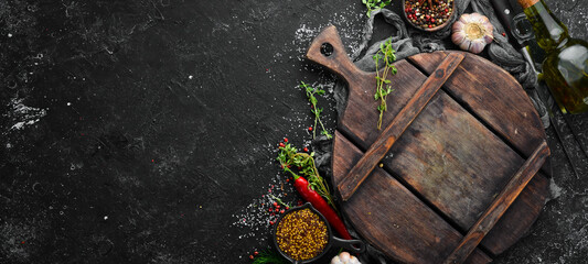 Black kitchen banner with board, spices and herbs. Top view. Free space for text. Wall mural
