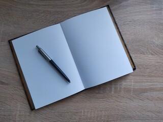 Obraz Długopis leżący na notatniku poety na jasnym biurku  - fototapety do salonu