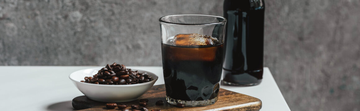 cold brew coffee with ice in glass and bottle near coffee beans on chopping board on white table, panoramic shot