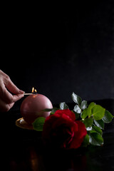 Still life with candle, rose and hand lighting a candle on a dark background