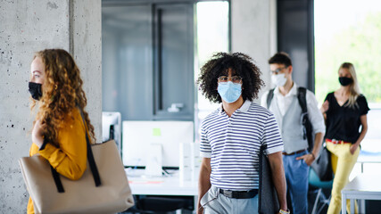 Aluminium Prints Equestrian Young people with face masks back at work in office after lockdown, walking.