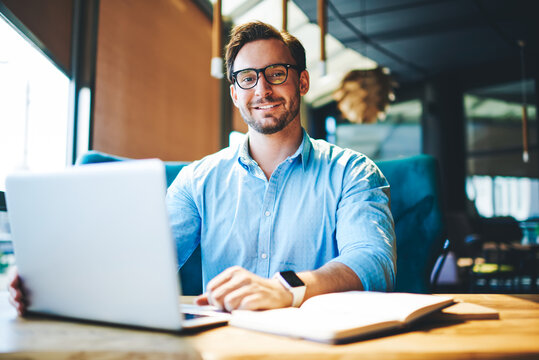 Portrait of cheerful businessman completing work on startup satisfied with making great job