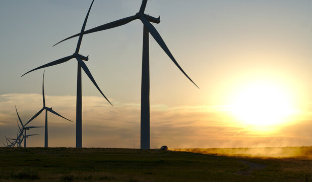 Renewable Energy wind turbines at sunset in West Texas as a truck drives across the landscape.