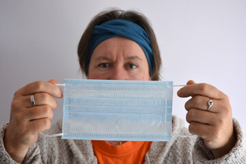 Woman holding a disposable 3ply non-surgical face mask with elastic loops, selective focus on the mask