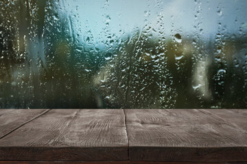 Wooden table near window on rainy day