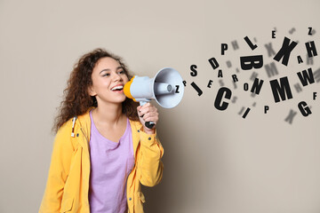 Young African-American woman with megaphone and letters on light background. Speech therapy concept