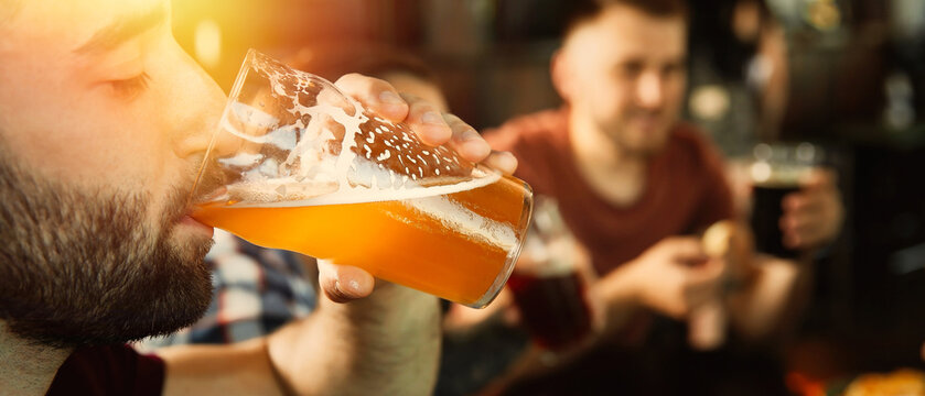 Young man drinking tasty beer in pub, space for text. Banner design