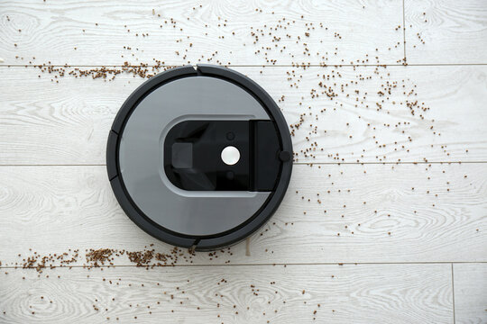 Modern robotic vacuum cleaner removing scattered buckwheat from wooden floor, top view