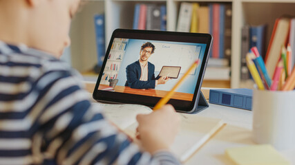 Door stickers Wall Decor With Your Own Photos Little Boy Uses Digital Tablet for Video Call with His Teacher. Screen Shows Online Lecture with Teacher Explaining Subject from Classroom. E-Education Distance Learning, Homeschooling. Over Shoulder