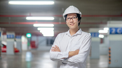 Asian civil engineer or construction worker man wearing protective safety helmet. Male architect working at construction site. Building and architecture concept