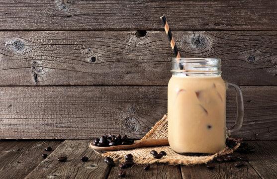 Summer iced coffee in a mason jar. Side view against a rustic dark wood background.