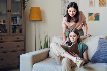 Curious teenage girl sitting in relaxed pose on sofa and reading book while mother supporting her hobby