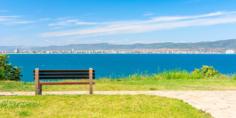 bench on the sunny beach shore. beautiful view from  paved footpath on the seaside. city and mountain in the distance beneath a blue sky with clouds
