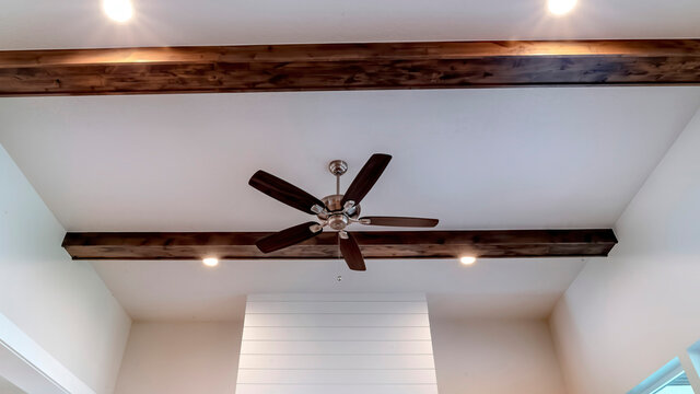 Panorama crop Ceiling fan with lights between decorative wood beams inside living room of home