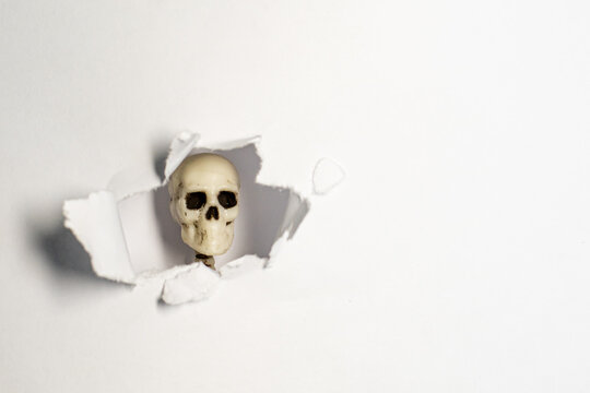 a torn window in white paper through which a skeleton skull is visible. sudden appearance of death