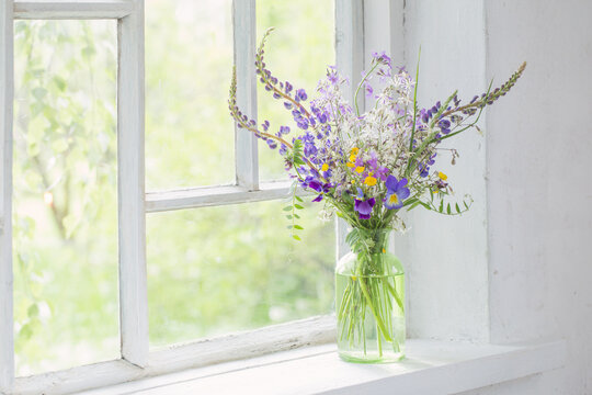 wild flowers in vase on white windowsill