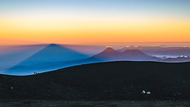 Sun rising over Guatemalan highlands with Volcan de Agua and Pacaya volcano in a distance seen from the top of Acatenango volcano. Scenic volcanic landscape of Guatemala.