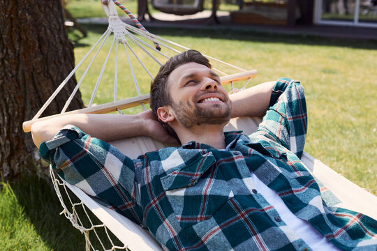 Young cheerful man lying in hammock outdoors
