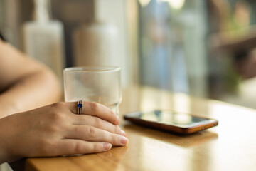 female hand in cafe table cozy picture with ring on fingers empty glass cup and unfocused phone on background