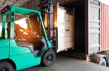 Forklift loading shipment pallet goods into container shipping truck. Road freight cargo by truck transportation.