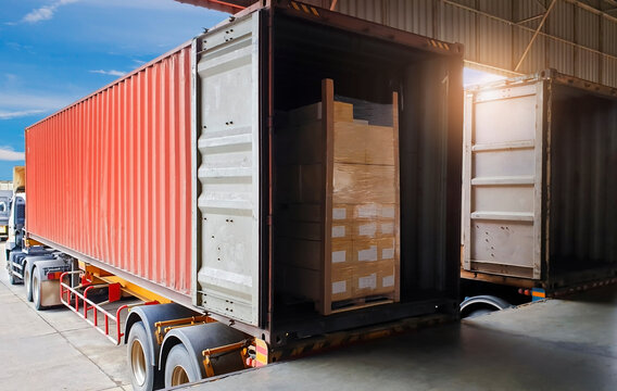 Road freight industry logistics and transportation. Trailer cargo truck parked at loading at dock warehouse. Stacked shipment boxes on pallet inside cargo container.