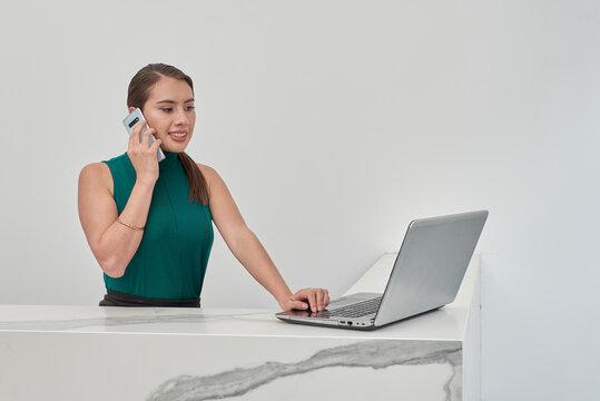 Recepcionista realizando llamada telefónica por celular mientras revisa su laptop, en un cubículo con acabado en mármol y muros de color blanco.