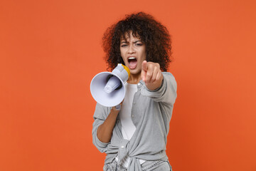 Angry young african american woman girl in gray casual clothes isolated on orange wall background. People lifestyle concept. Mock up copy space. Scream in megaphone, pointing index finger on camera.